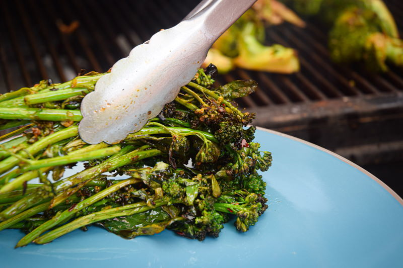 Grilled broccoli on blue plate.