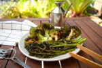 Grilled broccoli on dish and wooden table.