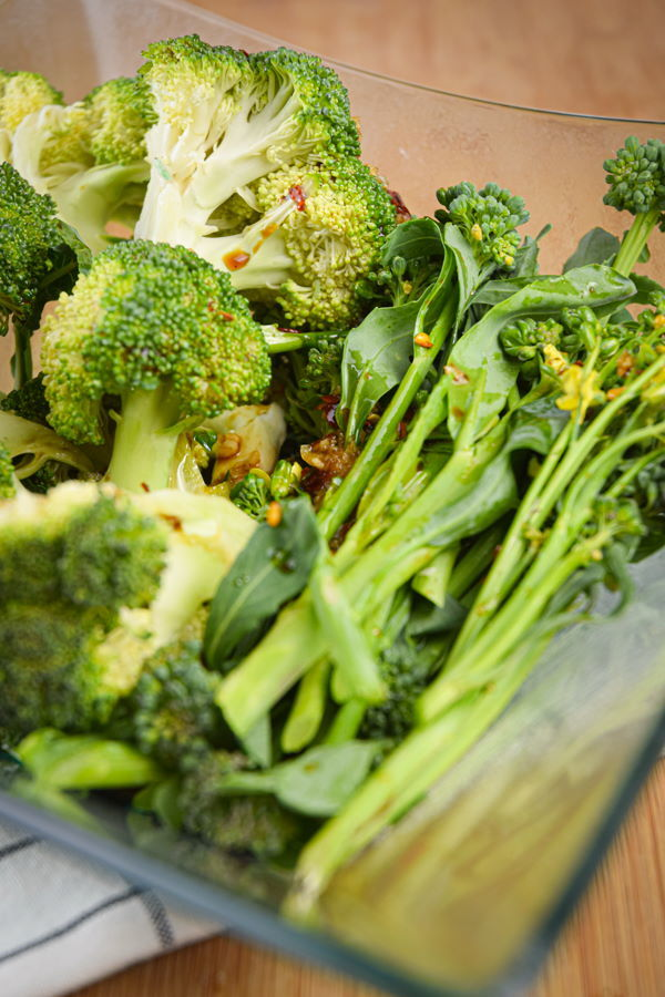 Broccoli in a glass dish with marinade.