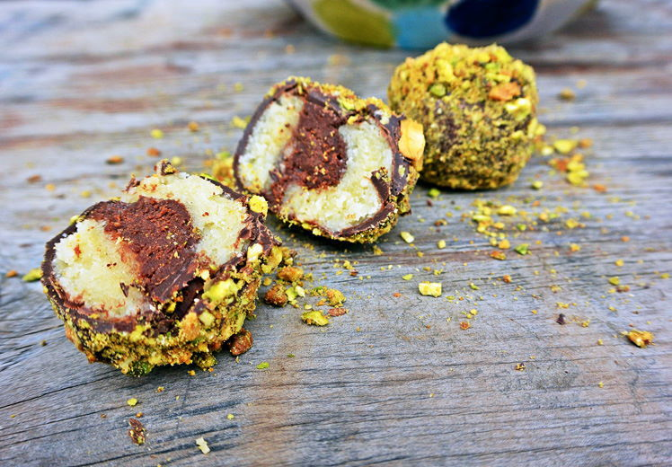 Marzipan truffles with pistachios on wooden background.