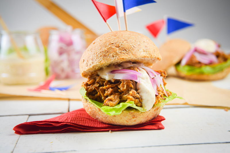 Pulled pork sliders with red white and blue flag toothpicks on white wooden background.