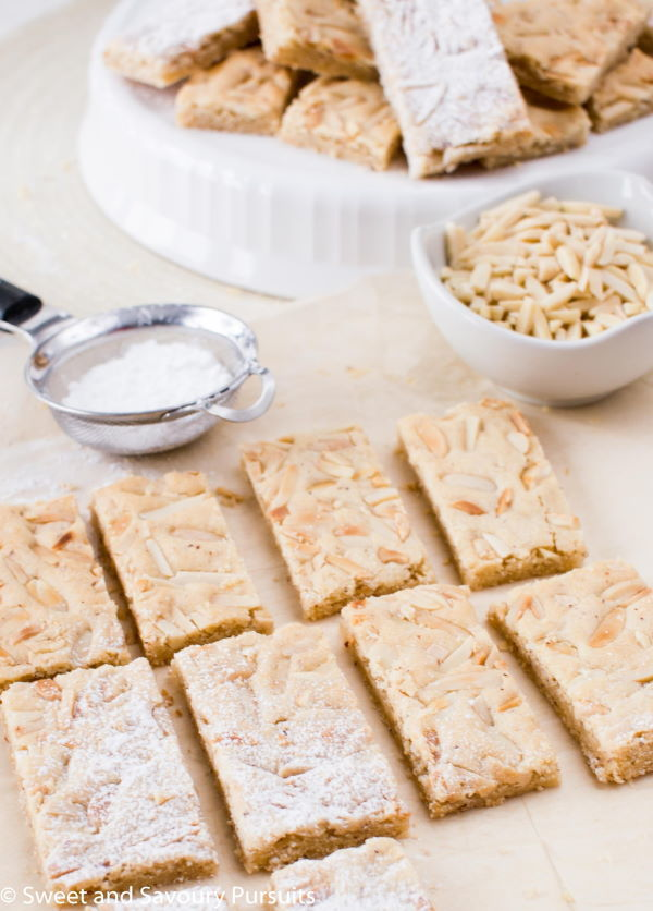 Chewy marzipan bars on parchment, slivered almonds in a bowl.