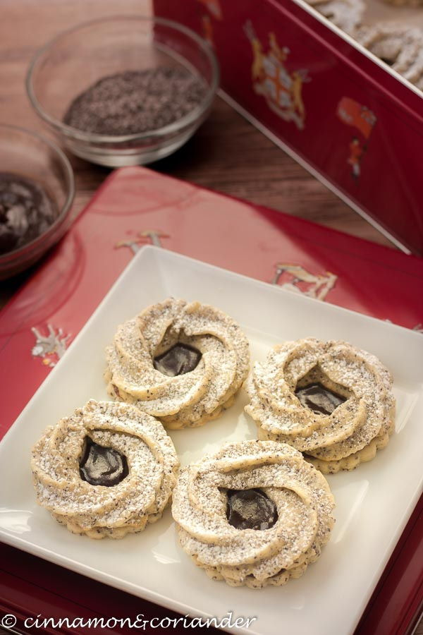 Marzipan cookies on a white plate, a red decorative box in the background.