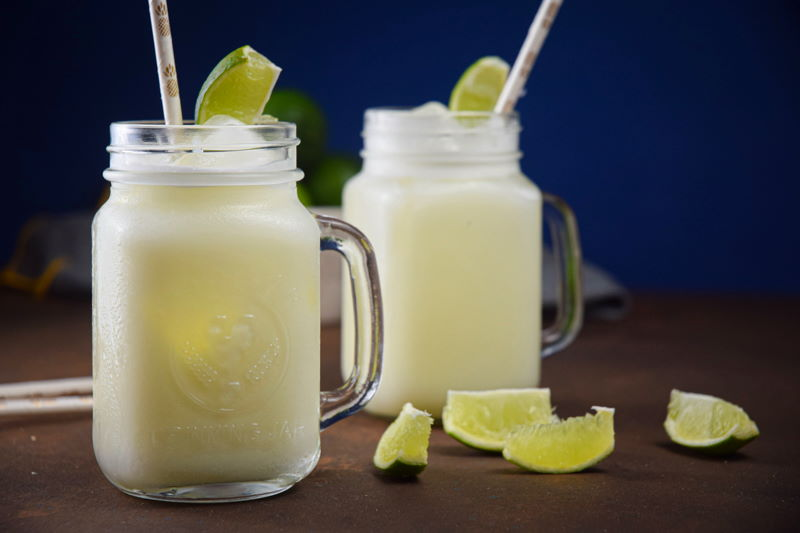 Brazilian lemonade in glass jars with lime wedges and paper straws.