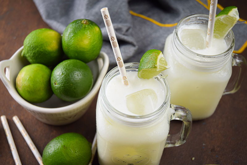 Brazilian lemonade in glass jars with lime wedges and paper straws, limes in a bowl on the side.