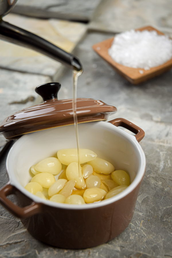 Fresh garlic cloves with oil and salt in small baking dish.