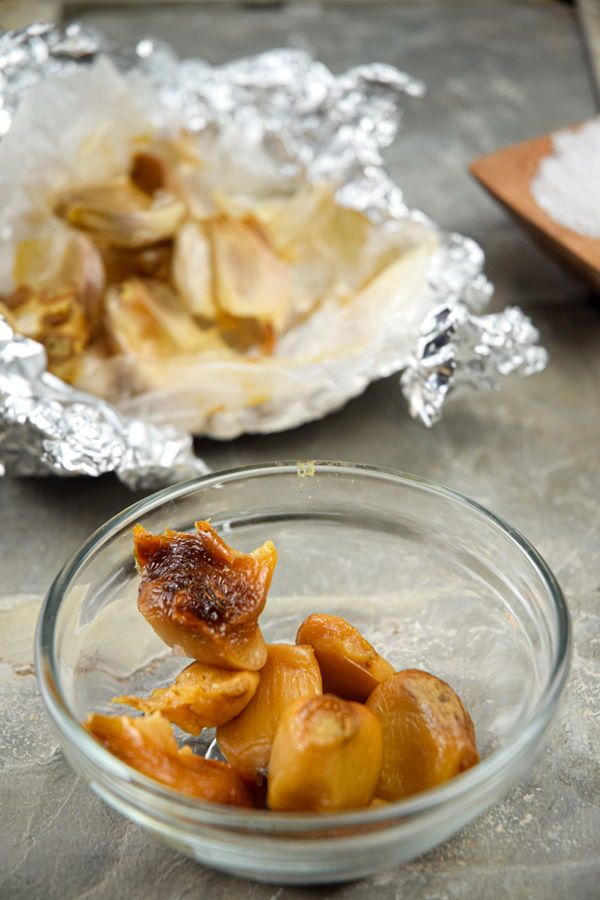 Roasted garlic cloves in a bowl, foil in the background.