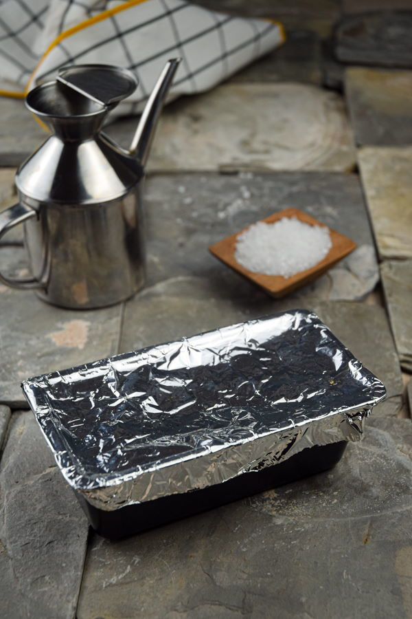 Garlic in a bread pan with foil on top, salt and oil in the background.