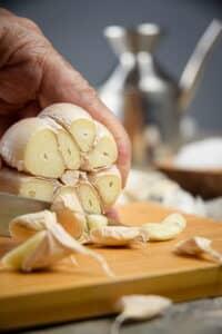 Fresh garlic head with the top cut off.