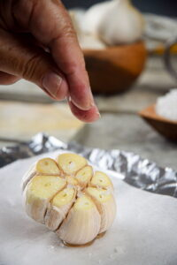 Fresh garlic head with salt on parchment and foil.