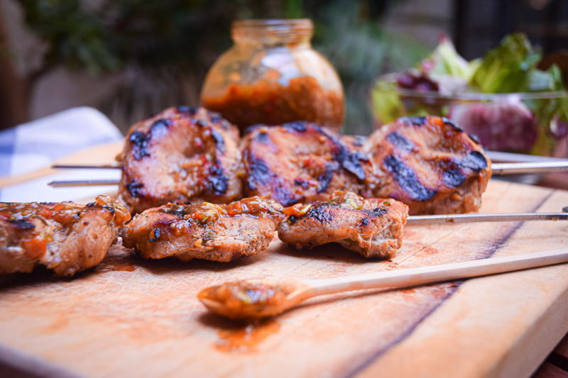 Grilled pork skewers on wooden cutting board with salad and jerk sauce on the side.