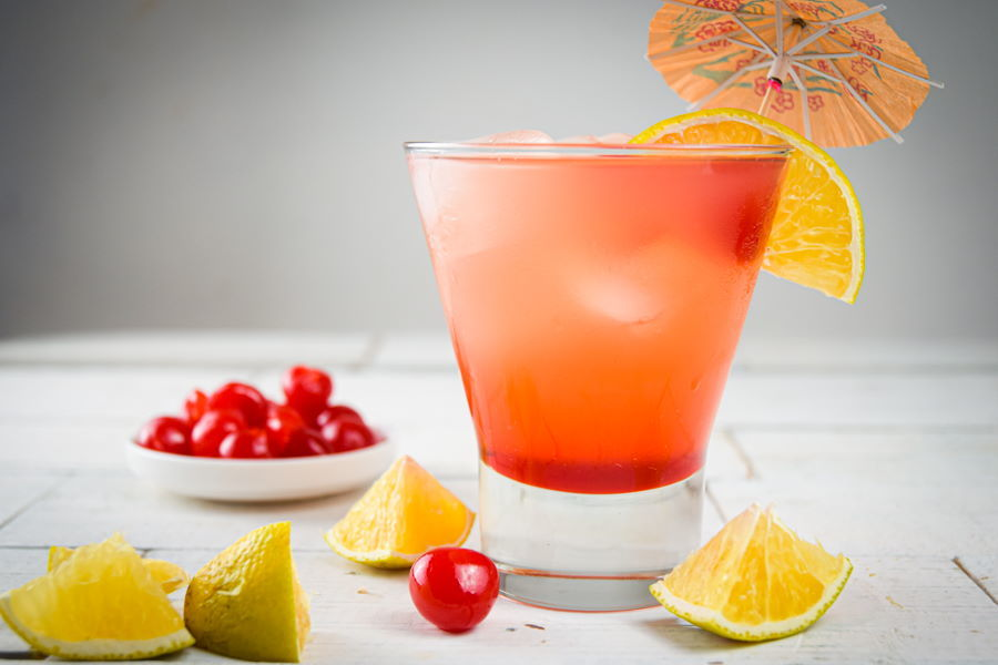 Shirley Temple Punch on white wooden background, maraschino cherries and lemons on the side.