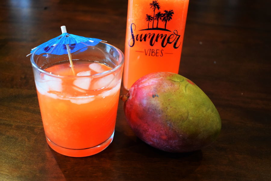 Summer mango soda in a glass with a mango on the side, wood background.