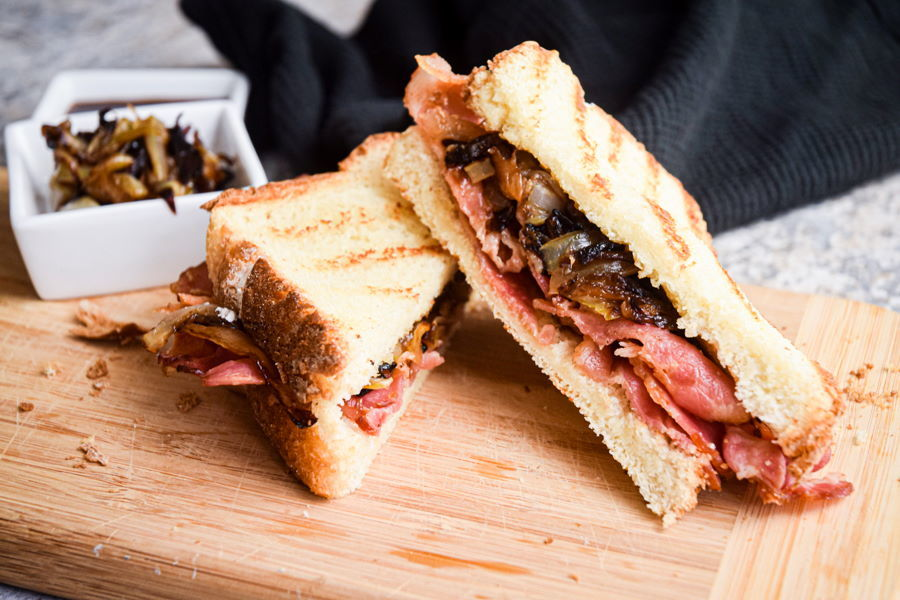 Bacon sandwich with carmelized onions on the side, wooden background.