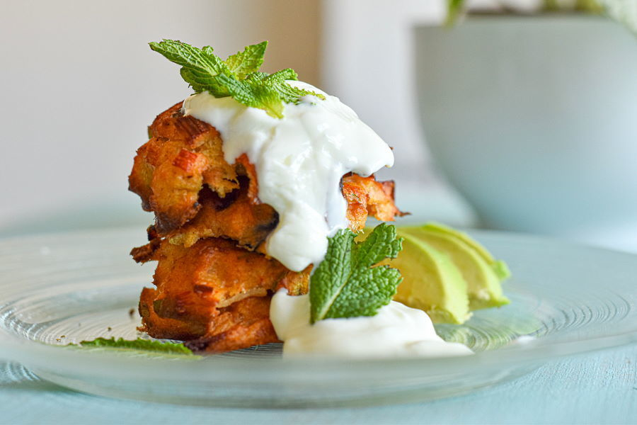 Crab cakes stacked on a clear glass plate with avocado and yogurt sauce.