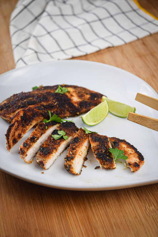 Sliced blackened chicken on a plate with lime wedges.