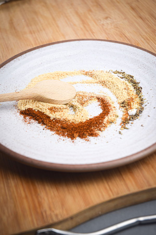 Blackening spices on a plate with a wooden spoon.