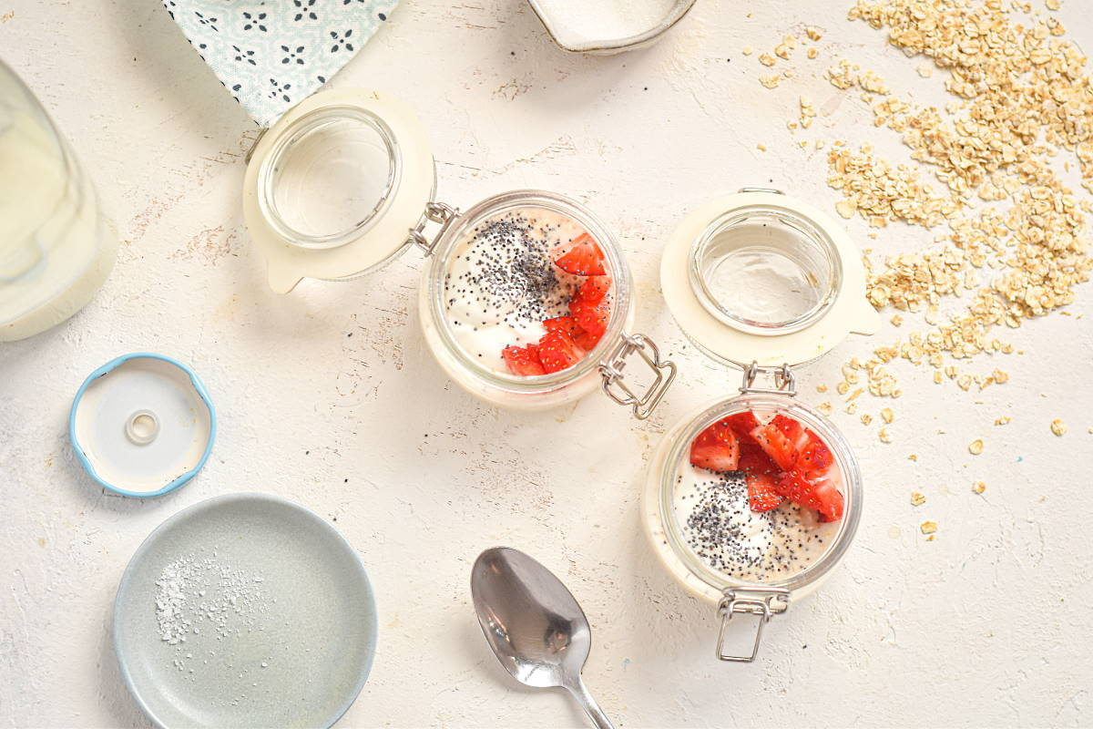 Porridge shots with fruit and chia topping, white background.