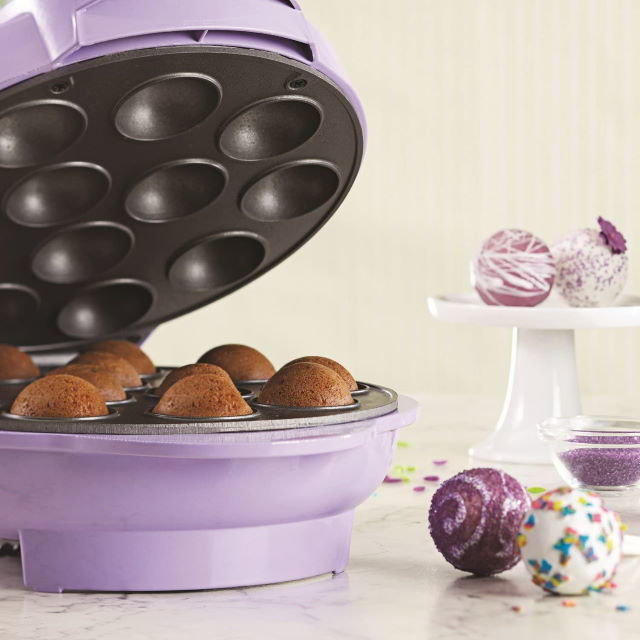 Purple Brentwood cake pop maker with lid open, cake balls on the side.