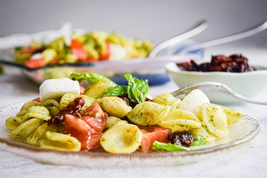Bruschetta pasta salad on clear glass plate, white background and small bowl of sun-dried tomatoes in the background.