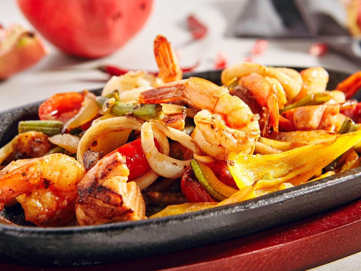 Cajun shrimp, sausage and veg in skillet.