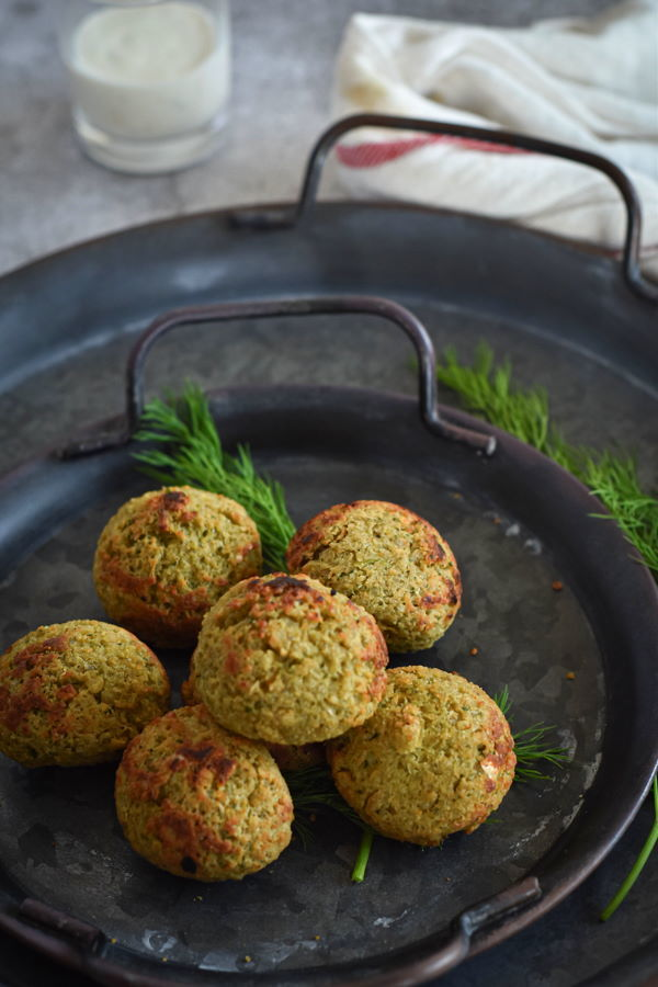 Falafels on a plate with yogurt sauce and fresh dill sprigs.