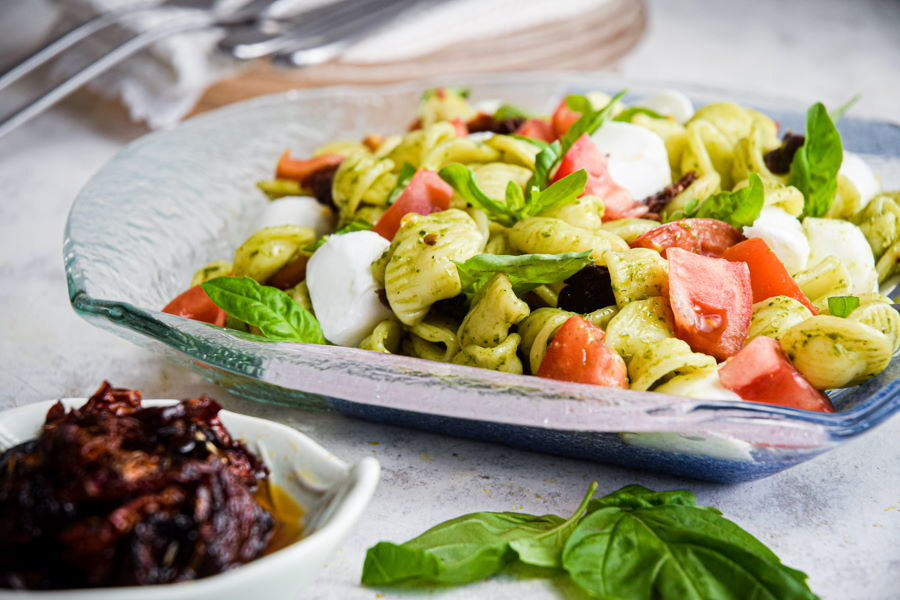 Caprese pasta salad on clear glass plate, white background.
