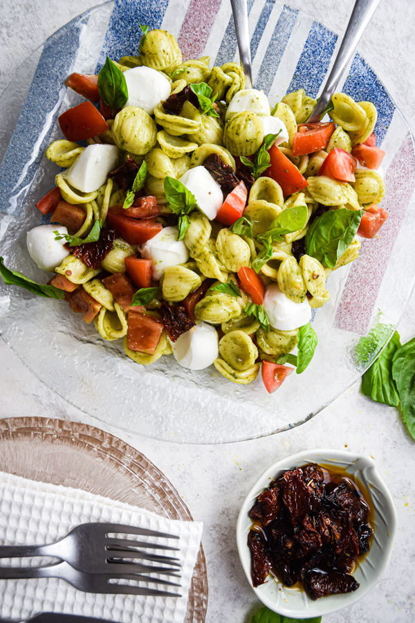 Caprese pasta salad on clear glass plate, white background, sun-dried tomatoes in a small bowl on the side.