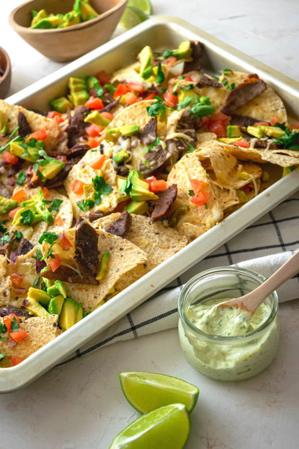 Carne Asada Nachos in a pan, with lime wedges, avocado and cilantro dip on the side.