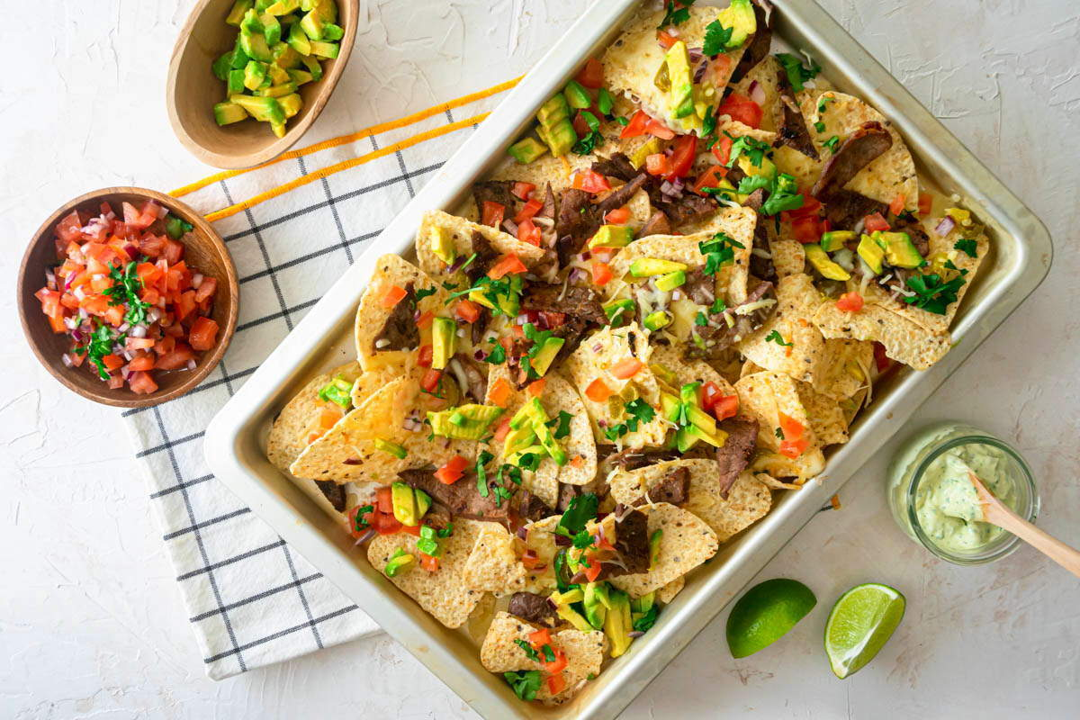 Carne Asada Nachos in a pan, with lime wedges, tomatoes, avocado and cilantro dip on the side.