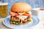 Chicken Fried Beef Burger with side sauce, blue background and glass of beer on the side.