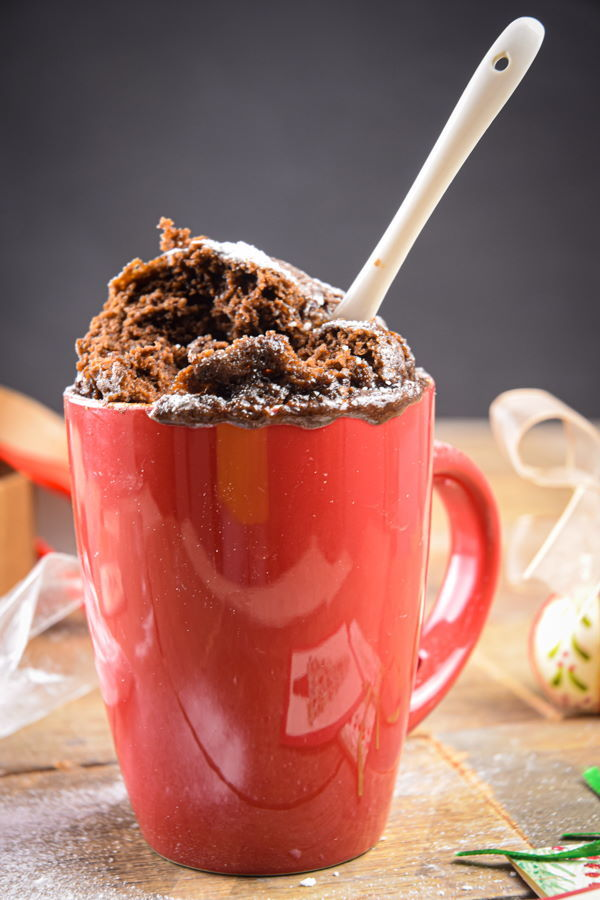 Chocolate mug cake in a red mug with white spoon, Christmas decorations in the background.