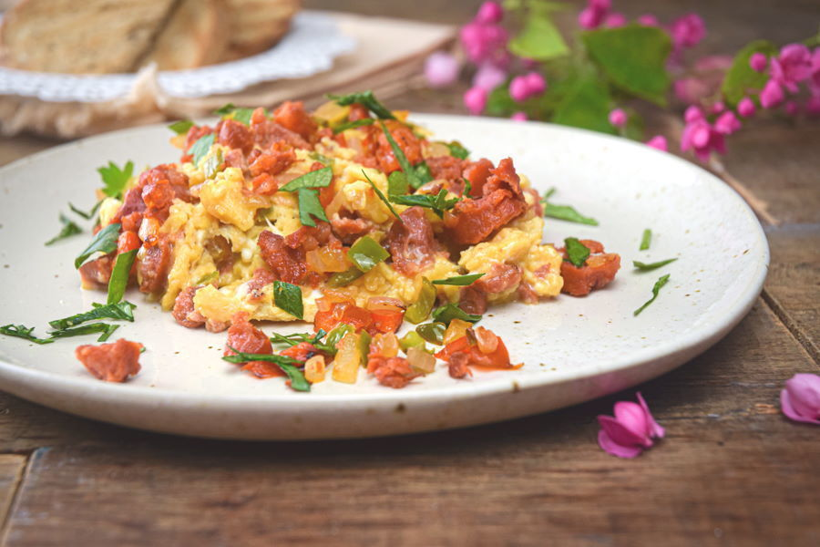 Chorizo and egg scramble on a white plate, small pink flowers scattered on the side.