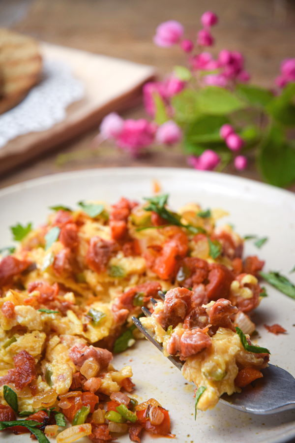 Chorizo and egg scramble on a white plate with a fork, small pink flowers on the side.