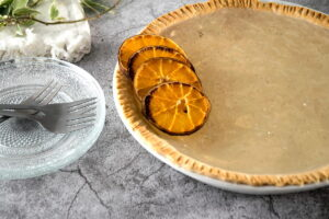 Clear pumpkin pie with dehydrated orange slices, forks and glass plates stacked on the side.