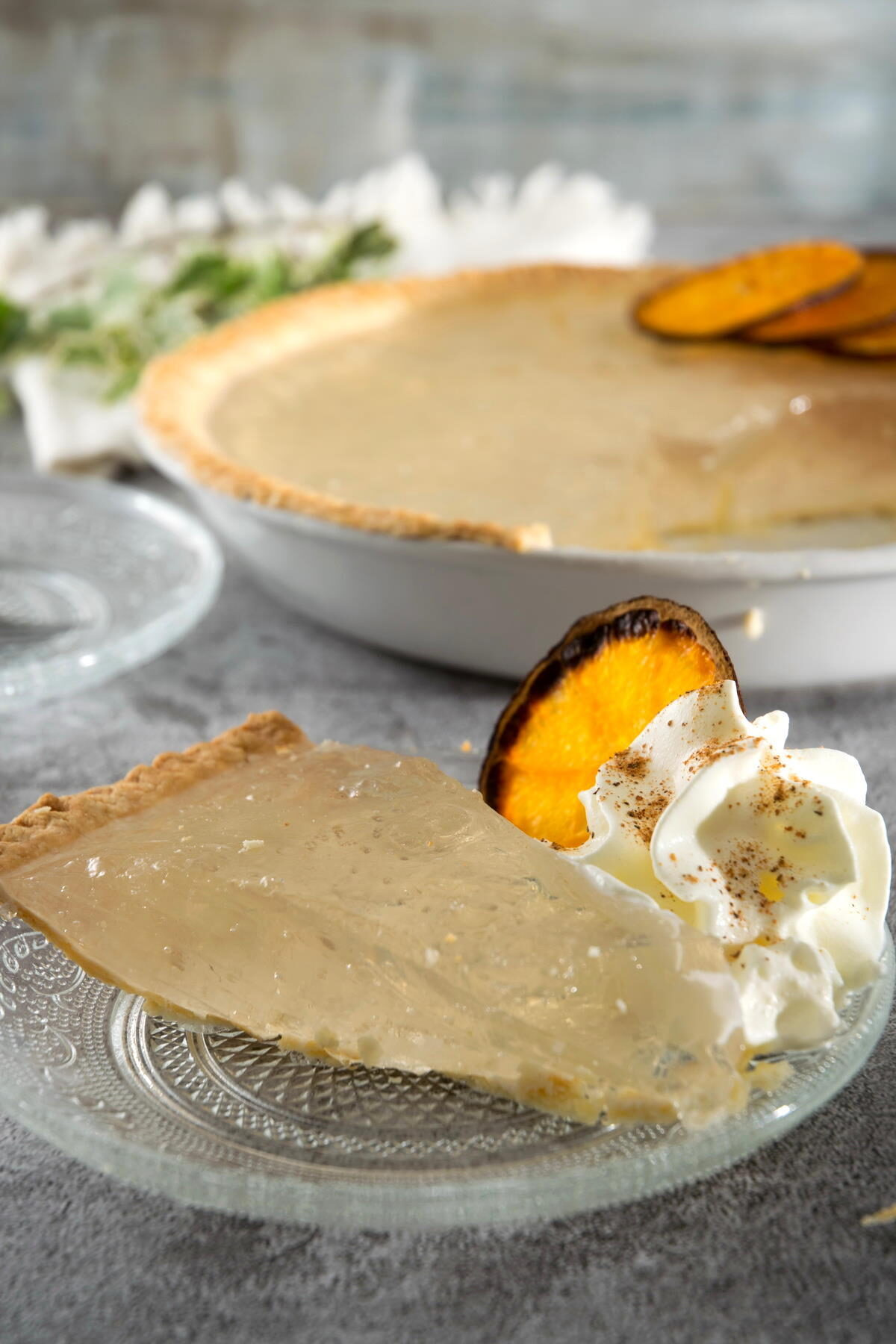 A slice of clear pumpkin pie on a clear glass plate with dehydrated orange slices and whipped cream.
