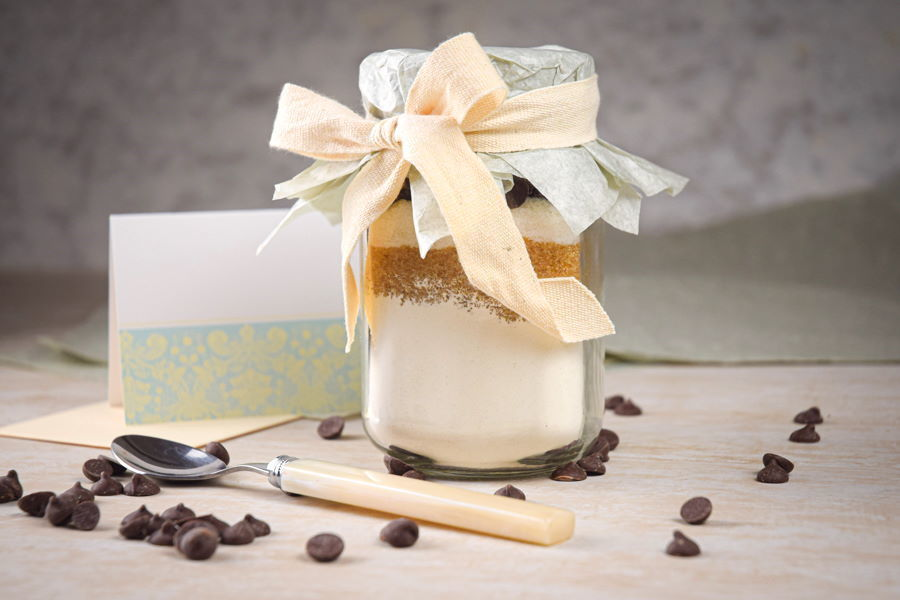 Chocolate chip cookie mix in a jar with chocolate chips, spoon and label on the side.