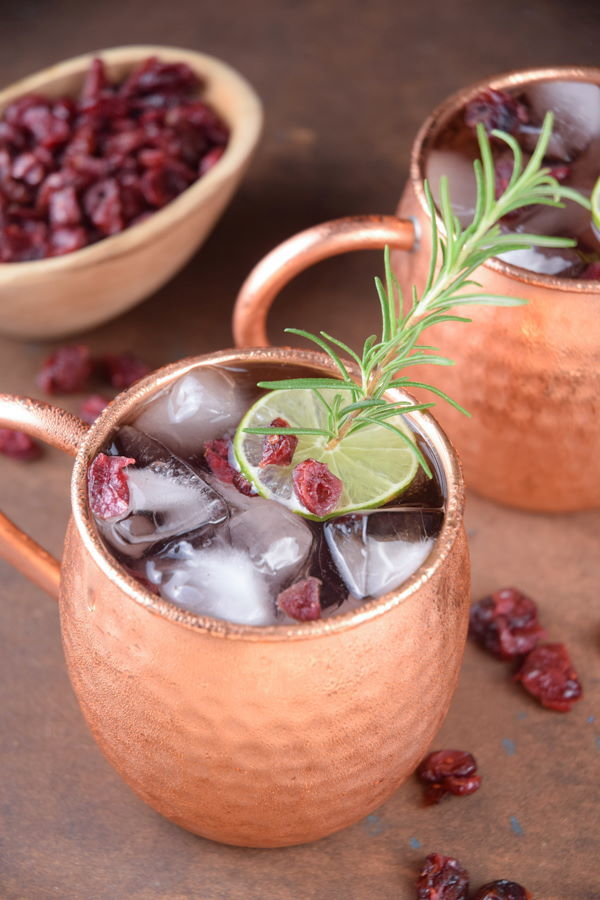 Cranberry Moscow Mule in copper mugs, garnished with cranberries, rosemary and lime slices.