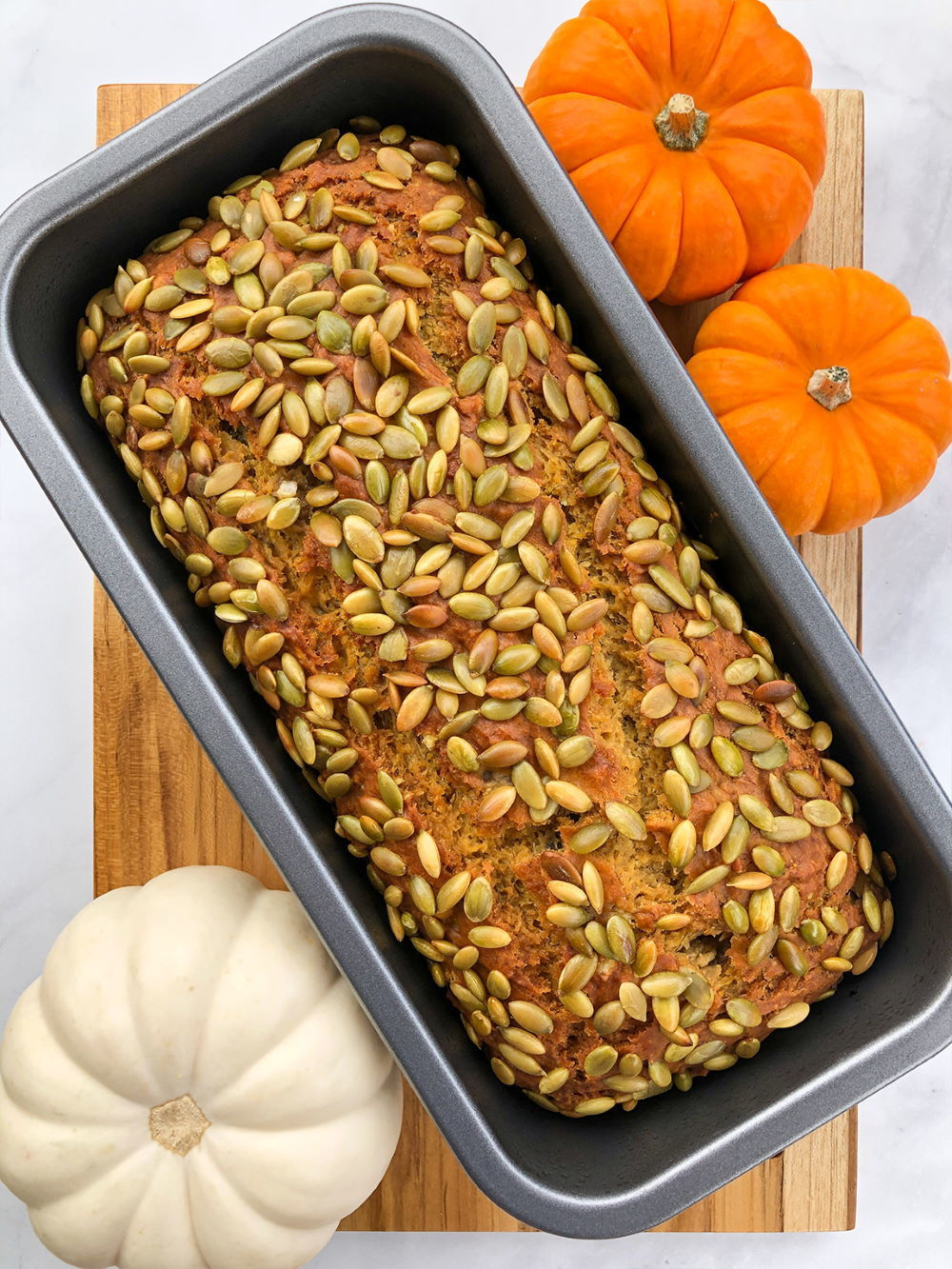 Pumpkin banana bread in loaf pan, gourds on the side.