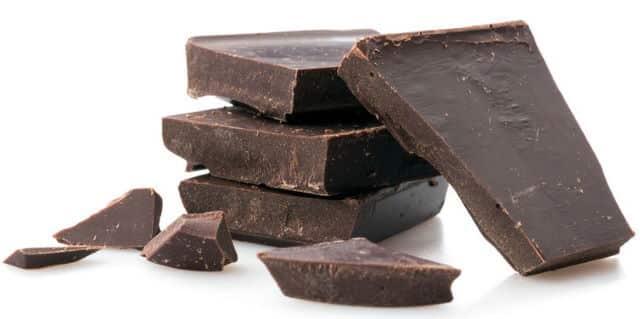 Dark chocolate pieces, white background.