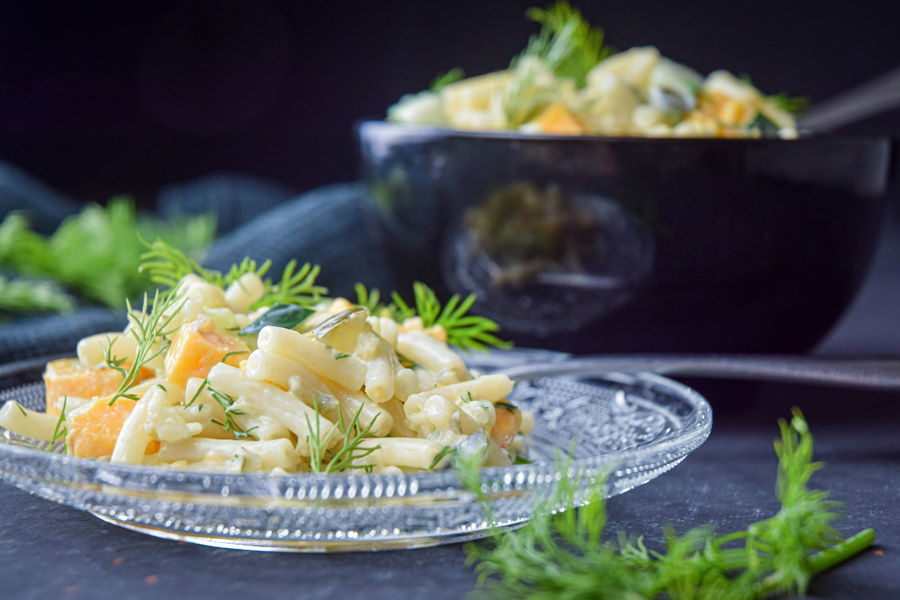 Dill pickle pasta salad garnished with fresh dill on a clear glass plate, dark background.
