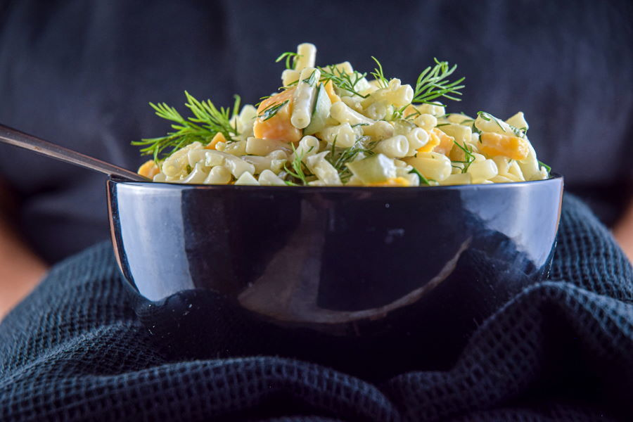 Dill pickle pasta salad garnished with fresh dill in a dark bowl, dark background.