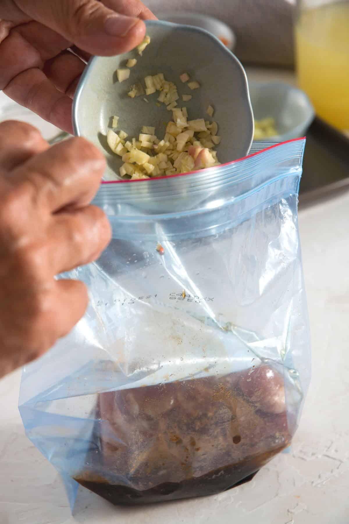 A ziptop bag with pork tenderloin, garlic and marinade.