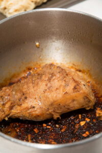 Seared pork tenderloin in a large pot.