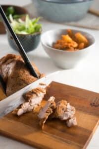Pork being sliced on a cutting board.