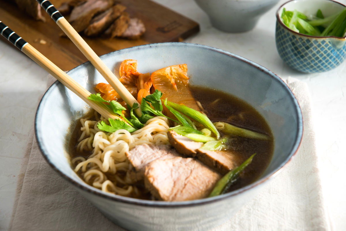 Kimchi ramen with pork slices and chopsticks in a bowl.