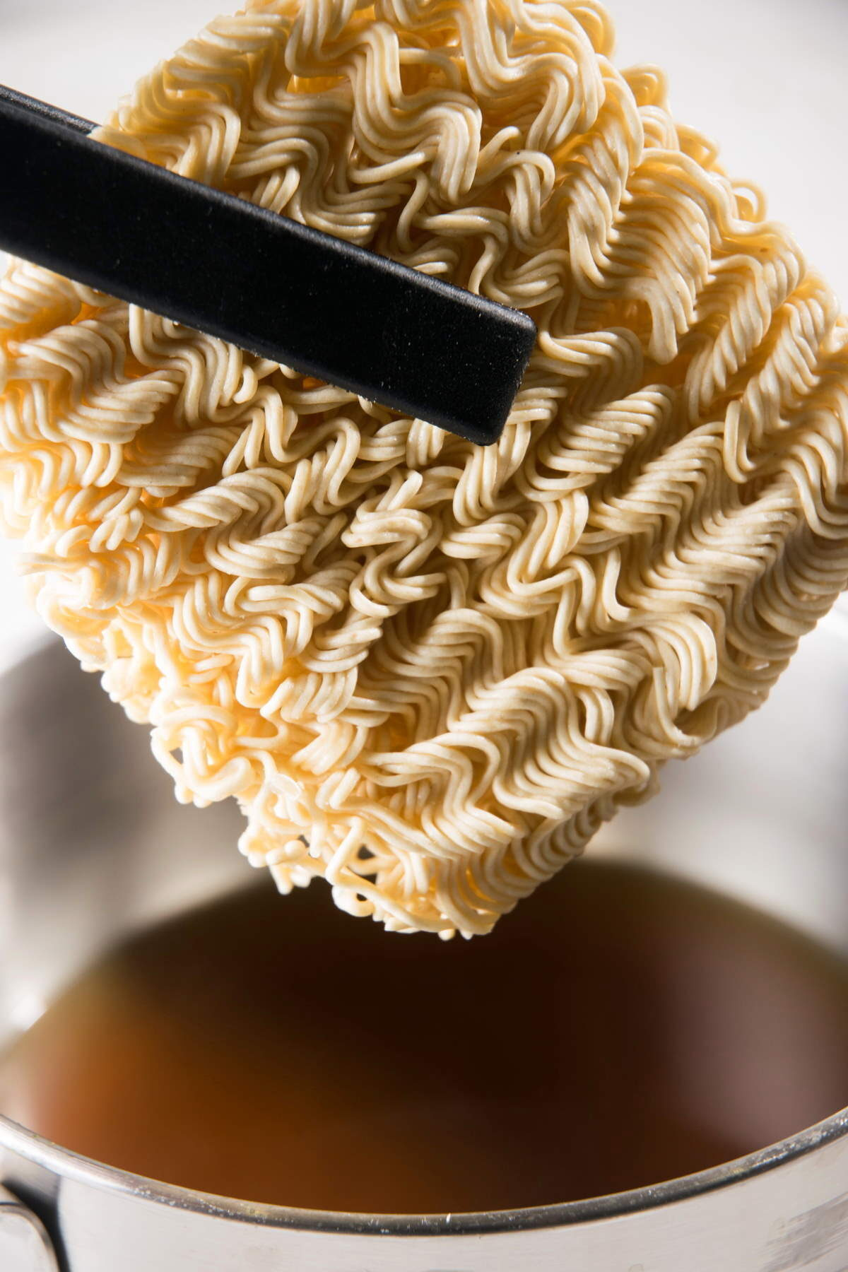 Instant ramen noodles in a pot with tongs.