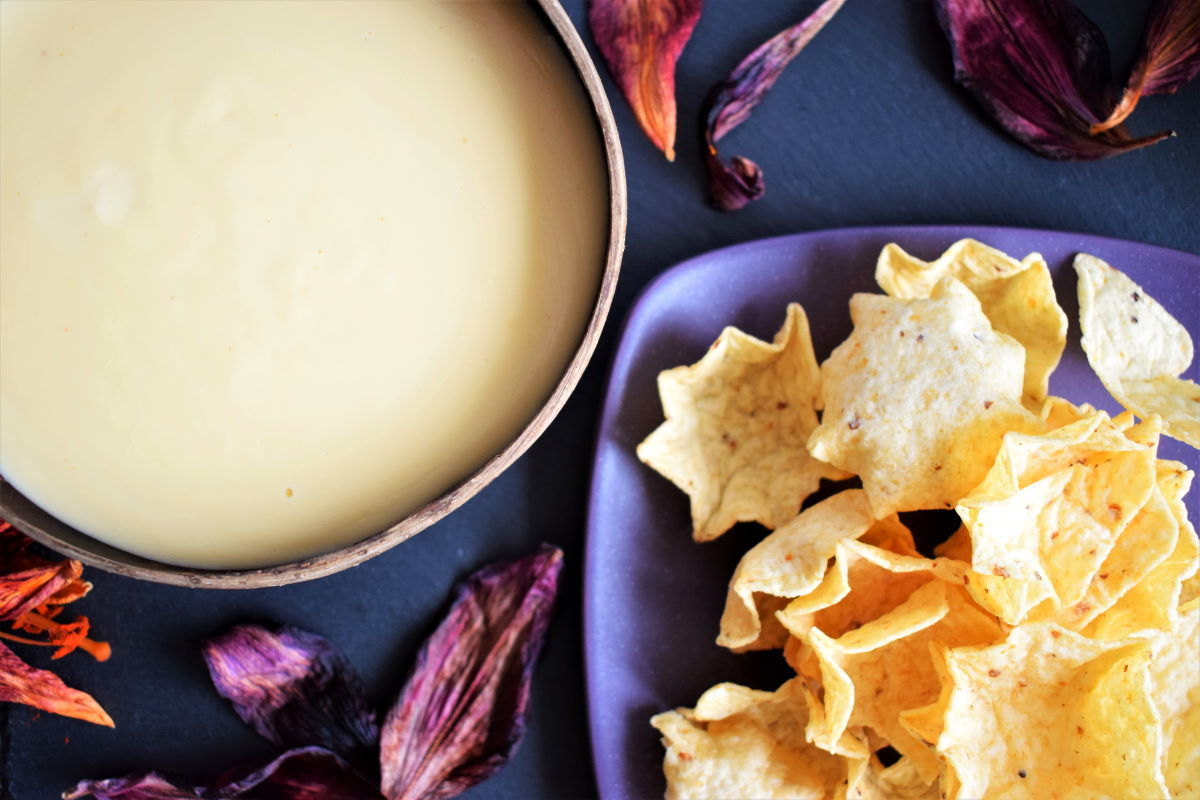 White cheddar nacho cheese sauce in a coconut bowl, tortilla chips and lily leaves on the side.