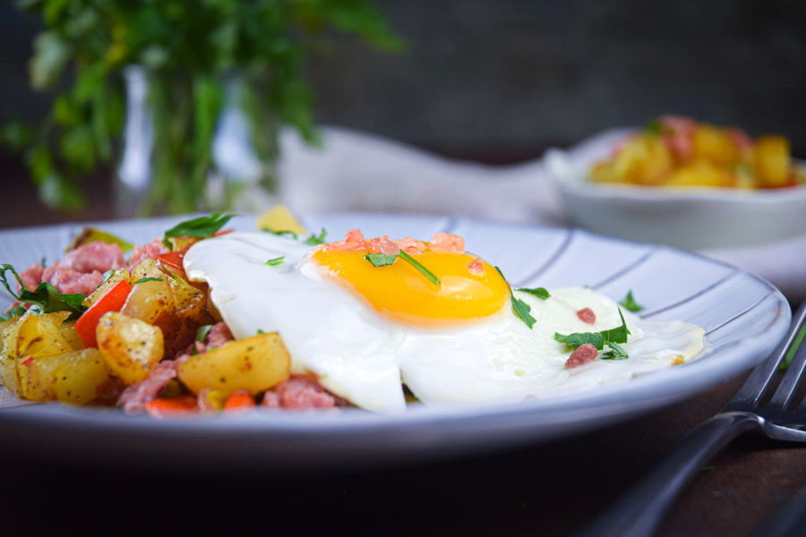 Electric skillet sausage and egg breakfast hash on a plate with a fork on the side, dark background.