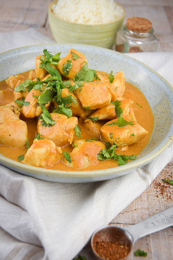 Electric Skillet Butter Chicken in a bowl with rice on the side, light wooden background.